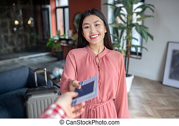 Cheerful dark-haired female taking airplane tickets from male hands, smiling