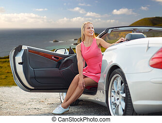 woman posing in convertible car over big sur coast