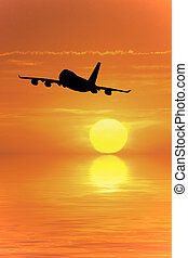 Travel - Airliner flying into the sunset over the ocean