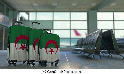 Travel suitcases with flag of Algeria. Algerian tourism...