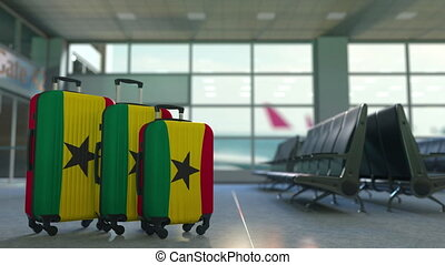 Travel suitcases with flag of Ghana. Ghanaian tourism...