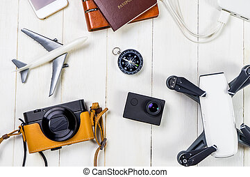 Travel technology accessories flat lay on white wood