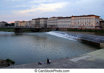 Travel to Florence, Italy. The sunset view on a river, a bridge and a dam.