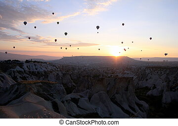 Travel to Goreme, Cappadocia, Turkey. The sunrise in the mountains with a lot of air hot balloons in the sky.
