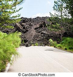 hardened lava flow on road on slope of Etna