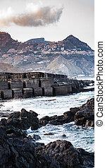 stone breakwater in Giardini Naxos town - travel to Italy -...