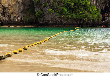 Travel to Krabi, Thailand. The scenic view on the sea with yellow buoys and a rock from Phra Nang Beach.