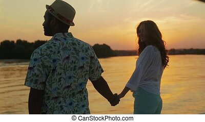 Guy and a girl enjoy the sunset from the yacht.