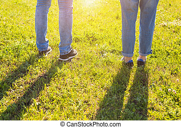 Travel together concept - stylish couple legs on sunny grass in meadow in summer