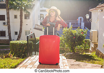 Travel, tourism and people concept - happy young woman in sunglasses and hat standing over the hotel background and carry a huge red suitcase