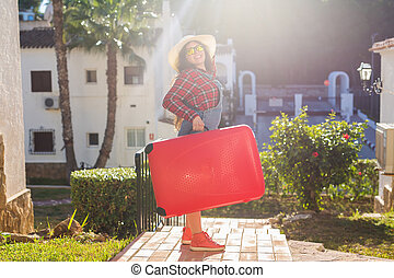 Travel, tourism and people concept - happy young woman in sunglasses and hat standing over the nature background and carry a huge red suitcase