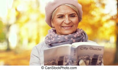 senior woman with city guide at autumn park - travel,...