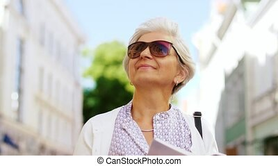 senior woman or tourist walking with city guide - travel,...