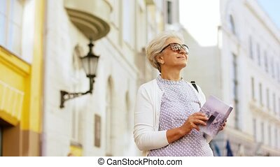 senior woman or tourist with city guide on street - travel,...