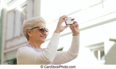 senior woman photographing by smartphone in city - travel,...