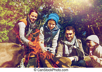 happy family roasting marshmallow over campfire