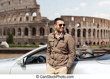 happy man near cabriolet car over coliseum - travel,...