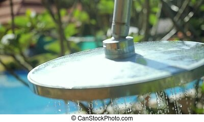 Travel, tourism, vacation and summer holidays concept outdoor beach shower with fresh water in slow motion through the garden. 1920x1080