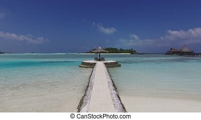 palapa and sunbeds on maldives beach pier over sea - travel,...