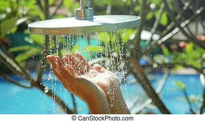 Travel, tourism, vacation, hygiene and summer holidays concept female hands washing in outdoor shower with fresh water in slow motion on pool background. 1920x1080