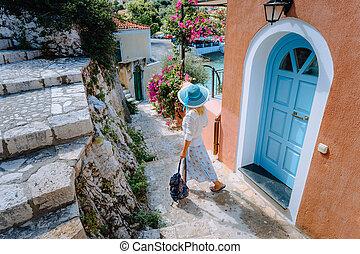 Travel tourist blonde woman with sun hat walking through...