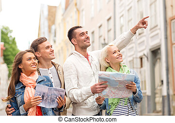 group of smiling friends with city guide and map - travel, ...