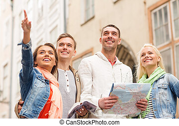 group of smiling friends with city guide and map - travel,...