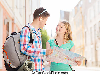 smiling couple with map and backpack in city - travel,...