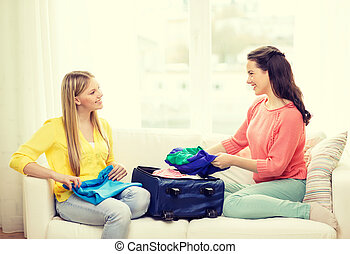 two smiling teenage girls packing suitcase at home