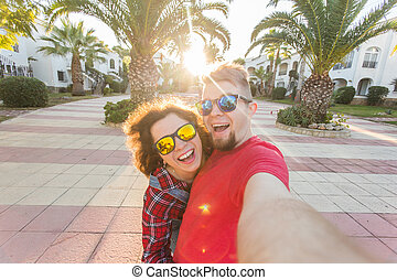 Travel, vacation and holiday concept - Happy traveling couple in love taking a selfie on phone