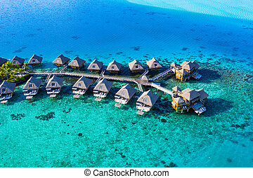 Travel vacation paradise aerial image with overwater bungalows in coral reef sea