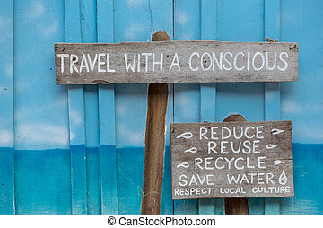 Travel with a conscious wooden sign on blue wooden...
