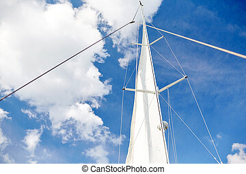 white sail on mast of boat over blue sky