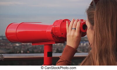 Travel: young woman tourist looking at city through coin-operated binoculars at sunset. Close-up shot, handheld, slow motion 60fps