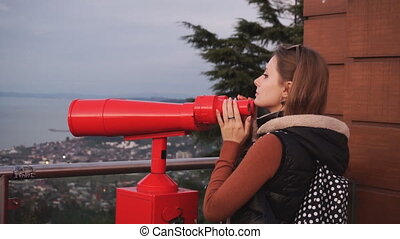 Travel: young woman tourist looking at city through coin-operated binoculars at sunset. Medium shot, handheld, slow motion 60fps