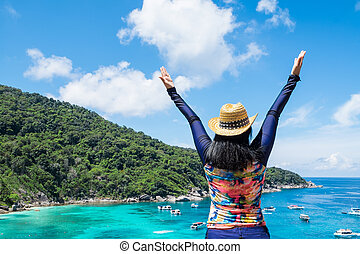 Traveler asian woman with colorful swimming suit raised arms to sky at top of mountain with blue ocean view and speed boat in sea, Summer vacation traveling.
