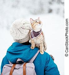 Traveler cat sitting on shoulder of woman in winter.