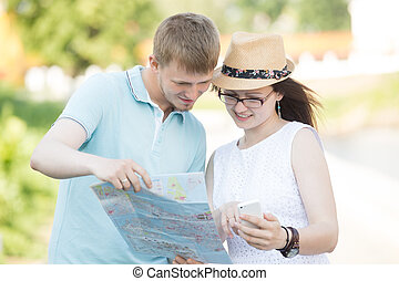 Traveler couple looking at map and phone for direction -...