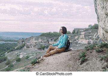 Traveler girl sitting on a stone.