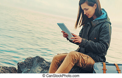 Traveler girl sitting on coast with digital tablet