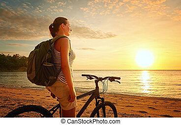 Traveler girl with backpack enjoying view of beautiful sunset.