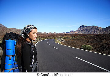 Traveler / hitchhiker - Young Female Traveler hitchhiking on...