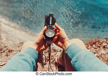 Traveler holding a compass on coastline - Traveler woman ...