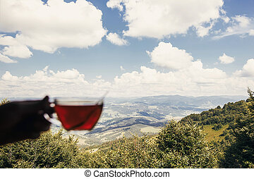 traveler holding glass of hot tea at window with view on mountains and sky. hipster man holding drink and relaxing on mountain top. summer vacation concept. focus on mountain