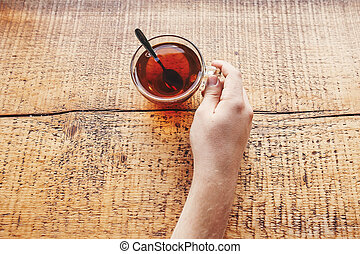 traveler holding glass of hot tea on wooden table, top view at window light. hipster man holding drink and relaxing on mountain top. summer travel and wanderlust. space for text