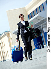 Traveler - Image of businesswoman in suit walking with her...