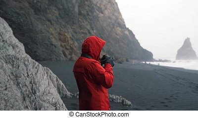 traveler in a bright jacket takes a photo.
