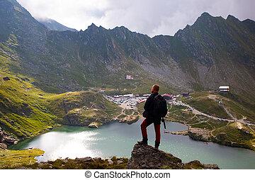 Traveler in high mountain of Fagaras watching over the Balea Lake.