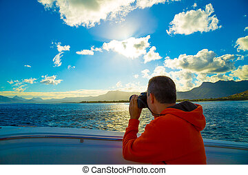 traveler in the orange jacket on the boat in the Indian Ocean near the coast of Mauritius