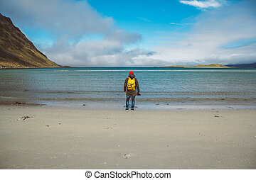 Traveler is a professional photographer taking over the landscape photo landscape. Wearing a yellow backpack in a red hat standing on a sandy beach on the background of the sea and mountains. Shoot from the back.